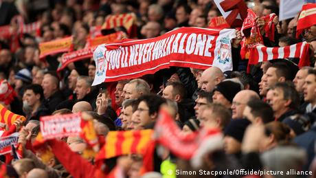 A fan of Liverpool FC holds up a scarf with its musical slogan You'll never walk alone printed on it