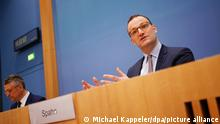 Jens Spahn with Lothar Wieler in the background