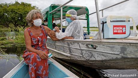 Mulher é vacinada em barco no Rio Negro, em Manaus
