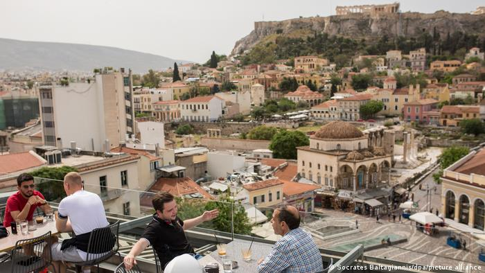 People sitting on a cafe terrace overlooking Athens and the Acropolis, Greece