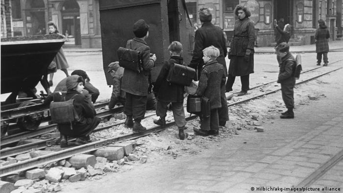 زندگی آرام آرام به جریان افتاده است. هیاهوی کودکان آلمانی در حیاط مدارس بار دیگر بهگوش میرسد. آنها در راه بازگشت به خانه به تماشای کار کارگران زن و مردی ایستادهاند که در حال تعمیر خط آهن هستند.