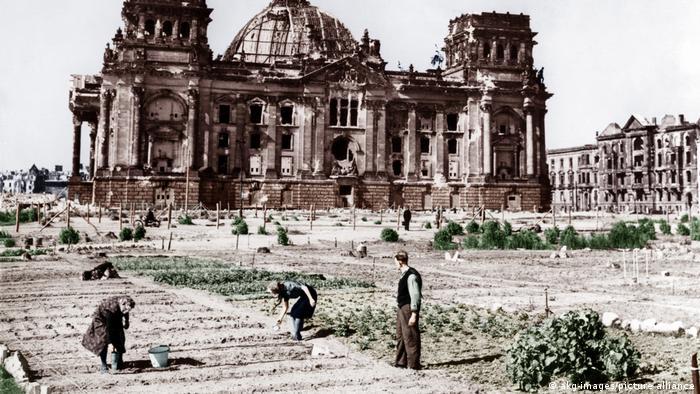 این ساختمان بمباران شده رایشتاگ (پارلمان آلمان) است. جنگ به پایان رسیده و مردمی که به مواد غذایی نیاز دارند خودشان دست به کار شدهاند و در محوطه جلوی پارلمان سبزی و صیفیجات کاشتهاند.