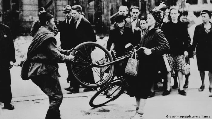 اینجا برلین است و یک سرباز روس دوچرخه یک زن آلمانی را میخواهد از او بگیرد. جنگ پایان گرفت و همه چیز به غنیمت گرفته شد، حتی زنان. تجاوز جنسی سربازان به زنان بخشی از جنگ بود که همه کشورهای درگیر سالها از سر شرم در مورد آن سکوت کردند.