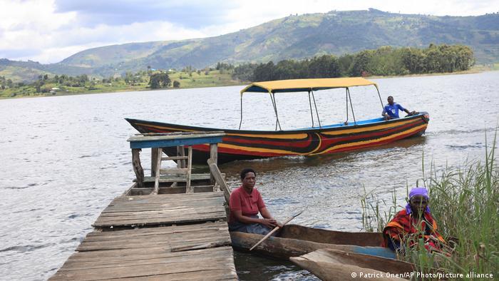 زنی که در پیشزمینه حضور دارد، واکسینه شده و اکنون در حال ترک جزیره بواما (Bwama) است. بواما بزرگترین جزیره در دریای بونیونی (Bunyonyi) در اوگاندا است. دولت این کشور آفریقای مرکزی هم تلاش میکند، ساکنان مناطق محروم را واکسینه کند.