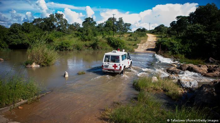 Simbabwe: Auf dem Weg in die Ortschaft Jari muss ein Impfteam eine überflutete Straße passieren