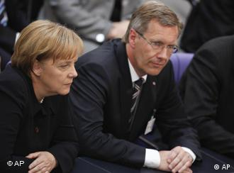 Wulff and Merkel sit next to each other, awaiting the results in Berlin.