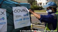 Airport workers spray the cargo of Covax COVID-19 vaccines