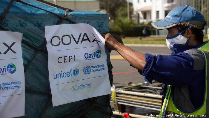 Airport workers spray the cargo of Covax COVID-19 vaccines on arrival in Antananarivo, Madagascar