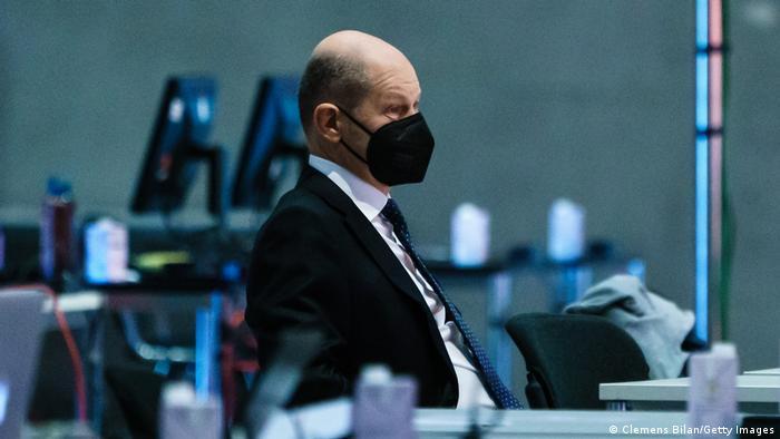 Olaf Scholz sitzt an einem Schreibtisch und wartet auf seinen Auftritt auf dem Parteitag.