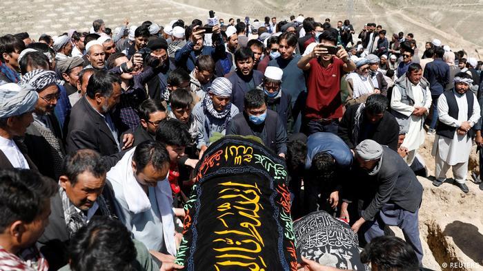 Eien Gruppe von Mensche in Afghanistan trägt einen Sarg zu Grabe | Massenbegräbnis nach Anschlag in Kabul