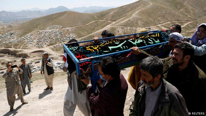 Men carry the coffin of one of the victims of an explosion outside a girls' school in Kabul, Afghanistan
