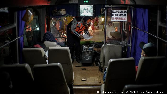 Polisi memeriksa penumpang bis di pos penyekatan Kedungwaringin, Bekasi, Minggu (09/05) malam