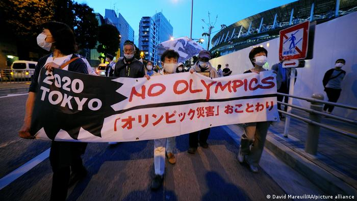 People march through Tokyo with a banner reading 'No Olympics'