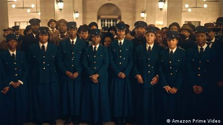 A scene from 'The Underground Railroad': the image is filled with Black people wearing train conductor uniforms, along with passengers behind them, all facing the camera.