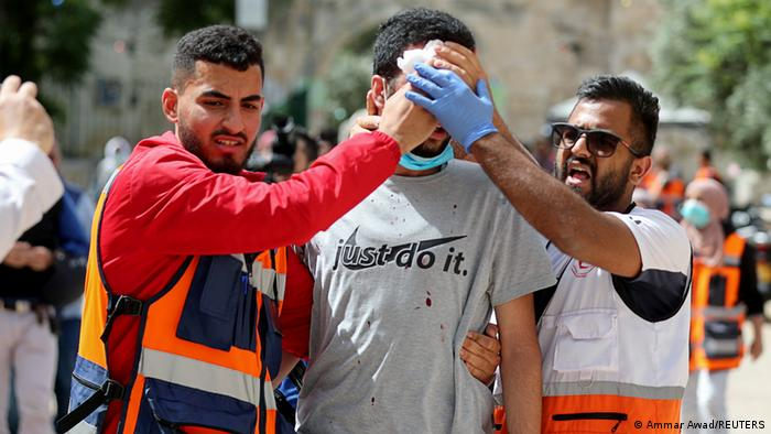 Medics tend to a wounded Palestinian during clashes with Israeli police at the compound that houses Al-Aqsa.