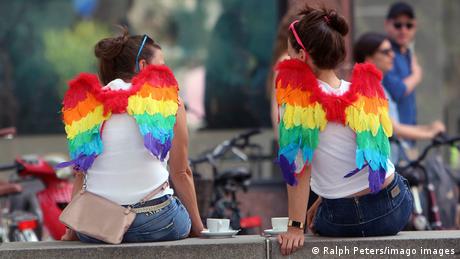 Symbolbild Diversität: Zwei Frauen mit Flügeln in Regenbogenfarben sitzen auf einer Mauer beim Kaffee