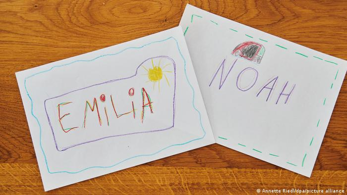The names Emilia and Noah in children's writing on paper