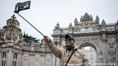 A tourist takes a selfie in front of the Ottoman-era Dolmabache Palace in Istanbul