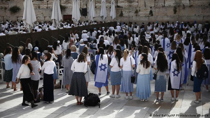 Jewish women some covered with Israeli flags pray during Jerusalem Day