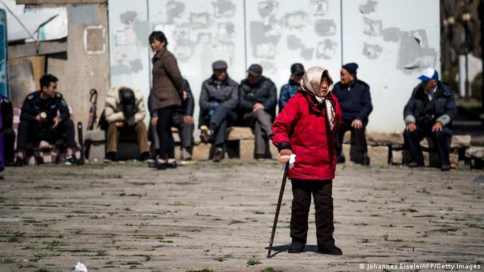 An elderly woman walks along a street in Shanghai