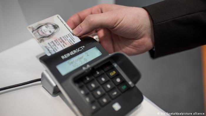 A person uses a digital ID card with a card reader