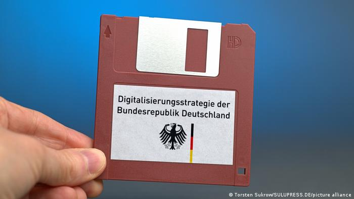 A 3.5 inch floppy disk with a German government logo and a label captioned Digitalization strategy of the Federal Government of Germany in German.