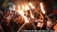 Palestinians light torches during a protest against attacks by Israeli police