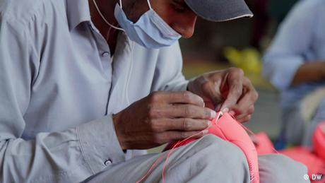 Man sewing a soccer ball
