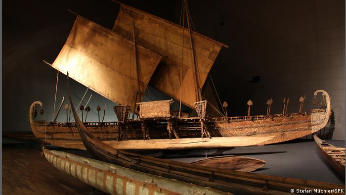 A wooden boat with sails
