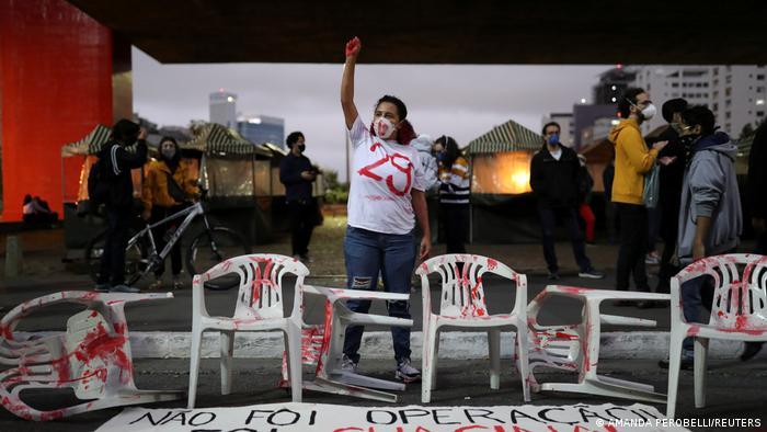 Eine Frau hinter einem Plakat reckt eine blutige Faust in die Höhe