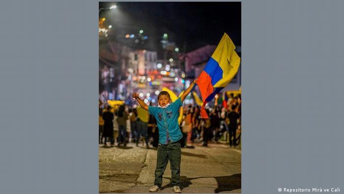 Niño llevando una bandera colombiana en San Agustín, Colombia.