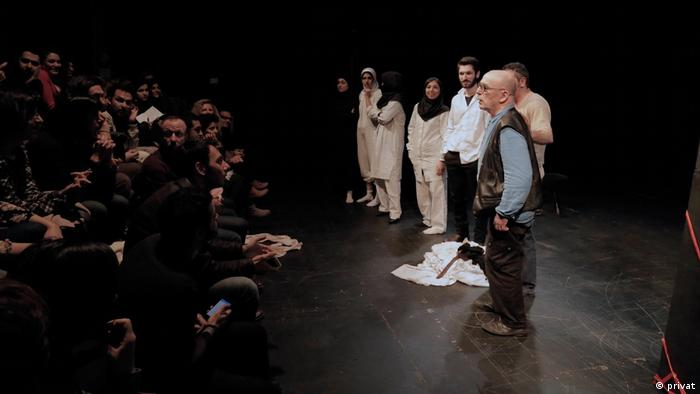 From a stage in Tehran, a man addresses the audience standing beside a group of transgender actors