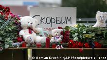 Цветы и свечи в память о погибших во время нападения на гимназию в Казани