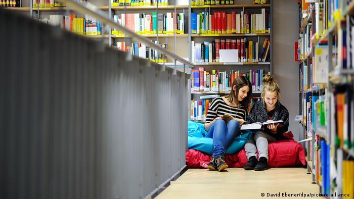 Две девочки рассматривают книгу в библиотеке одной из школь в Карлштадте