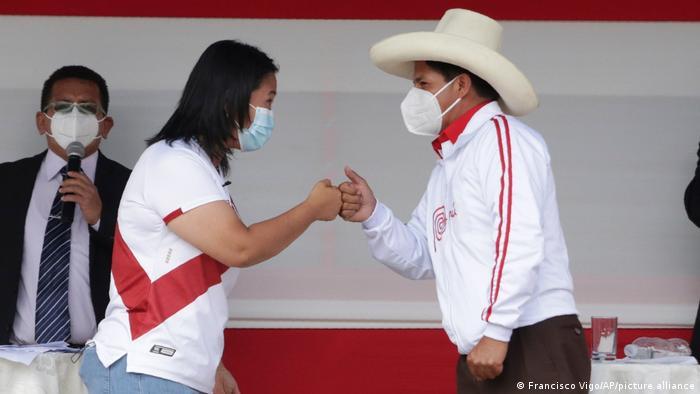 Presidential candidates Keiko Fujimori and Pedro Castillo fist bump at the end of a presidential debate.