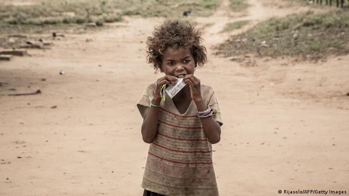 Menina muito suja coloca algo na boca. Ela está em frente a uma terra muito seca.