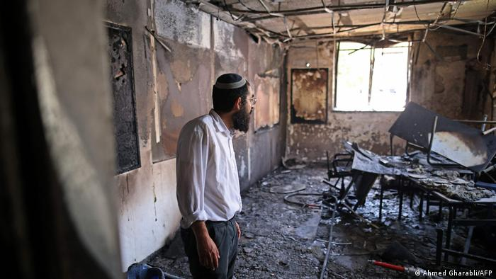 A Rabbi inspects the damage inside a torched religious school