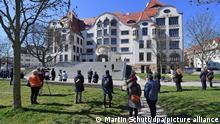 Einige Menschen stehen 19 Jahre nach dem Amoklauf am Gutenberg-Gymnasium bei einem stillen Gedenken vor dem Schulgebäude. Am 26. April 2002 hatte ein Schüler 16 Menschen erschossen und sich dann selbst das Leben genommen.