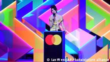 Singer Dua Lipa during her acceptance speech for the Best Album Brit Award, with a very colorful background.