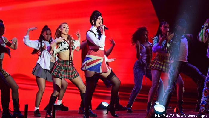 Dua Lipa performing with numerous dancers on stage at the Brit Awards at the O2 Arena in London.
