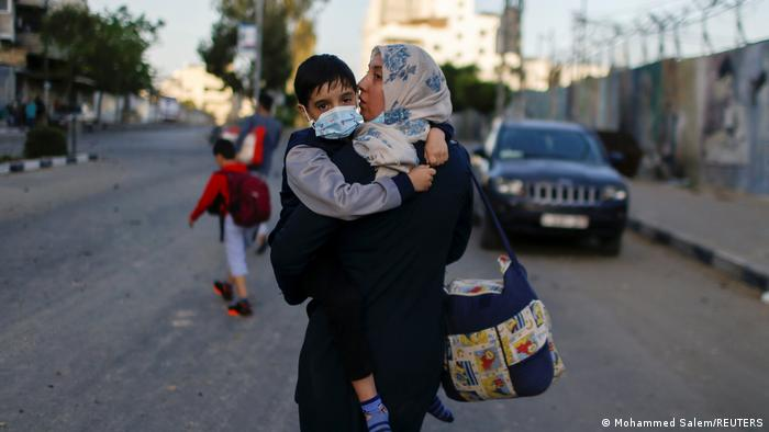 A Palestinian woman carrying her son