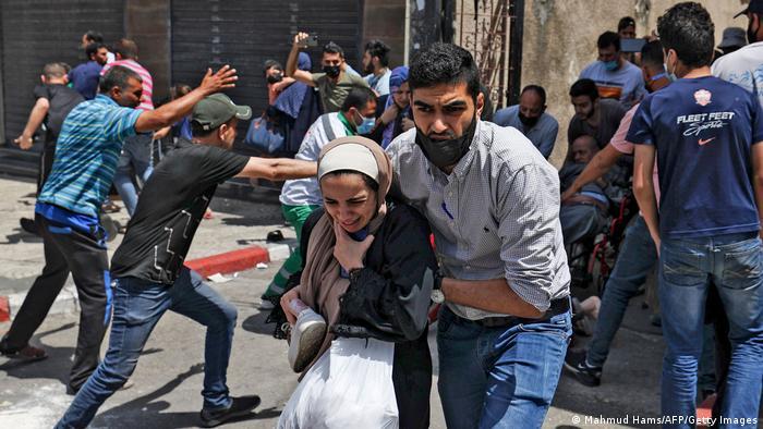 Palestinos evacuan su edificio de residencia atacado por misil israelí este 11 de mayo de 2021 en Gaza.