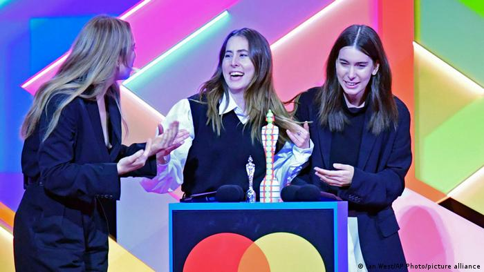 The US American band Haim: three young women smiling widely about their prize at the Brit Awards.