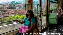 People wear face masks as they ride the tram in Medellin, Colombia, on May 12, 2020, amid the new coronavirus pandemic. - Colombia extended mandatory preventive isolation due to COVID-19 until at least May 25, however, in the city of Medellin kids between 6 and 17 years are allow to go outdoors for half hour a day. (Photo by JOAQUIN SARMIENTO / AFP) (Photo by JOAQUIN SARMIENTO/AFP via Getty Images)