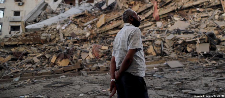 A Gazan man looks on at the remains of a tower building destoyed by Israeli air strikes