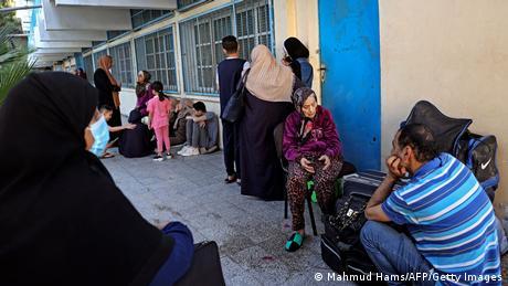 Menschen allen Alters sitzen und stehen vor einem Gebäude.