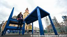 A person with COVID mask sits on huge blue chair by blue table in central Franfurt