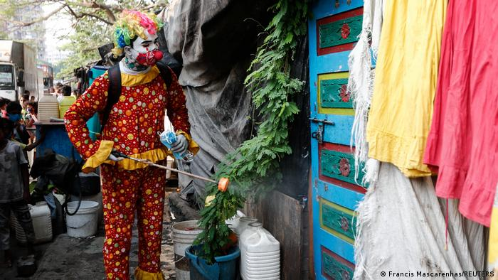 A man dressed as a clown and disinfecting in a Mumbai slum
