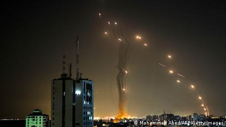 Raketen steuern auf andere Raketen am Nachthimmel über einer Stadt zu
