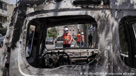Debris and torched vehicles litter the streets of the mixed Jewish Arab city of Lod following a night of Arab rioting against Jews
